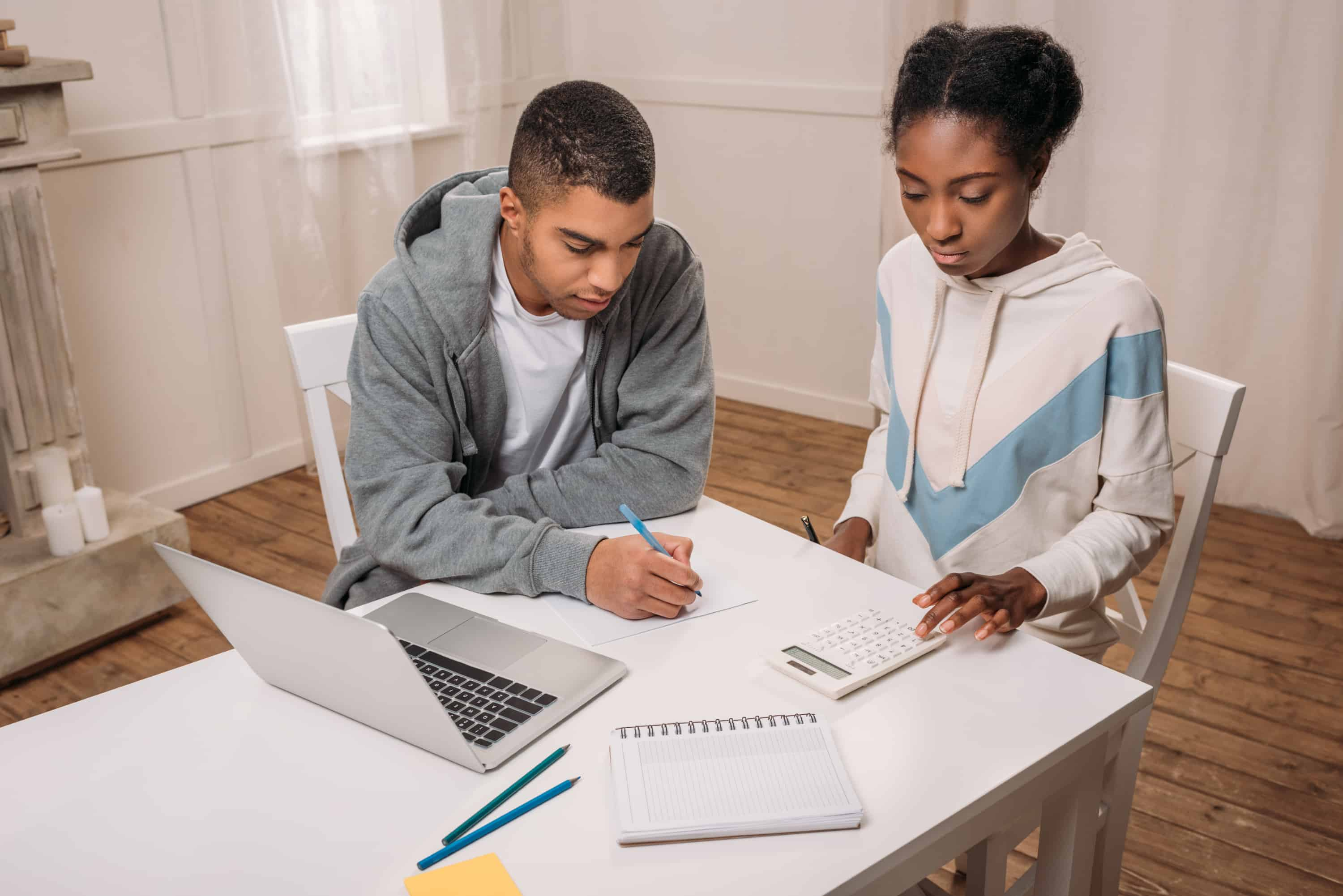 Black couple sitting at a white table calculating how much of a credit card balance transfer they can do