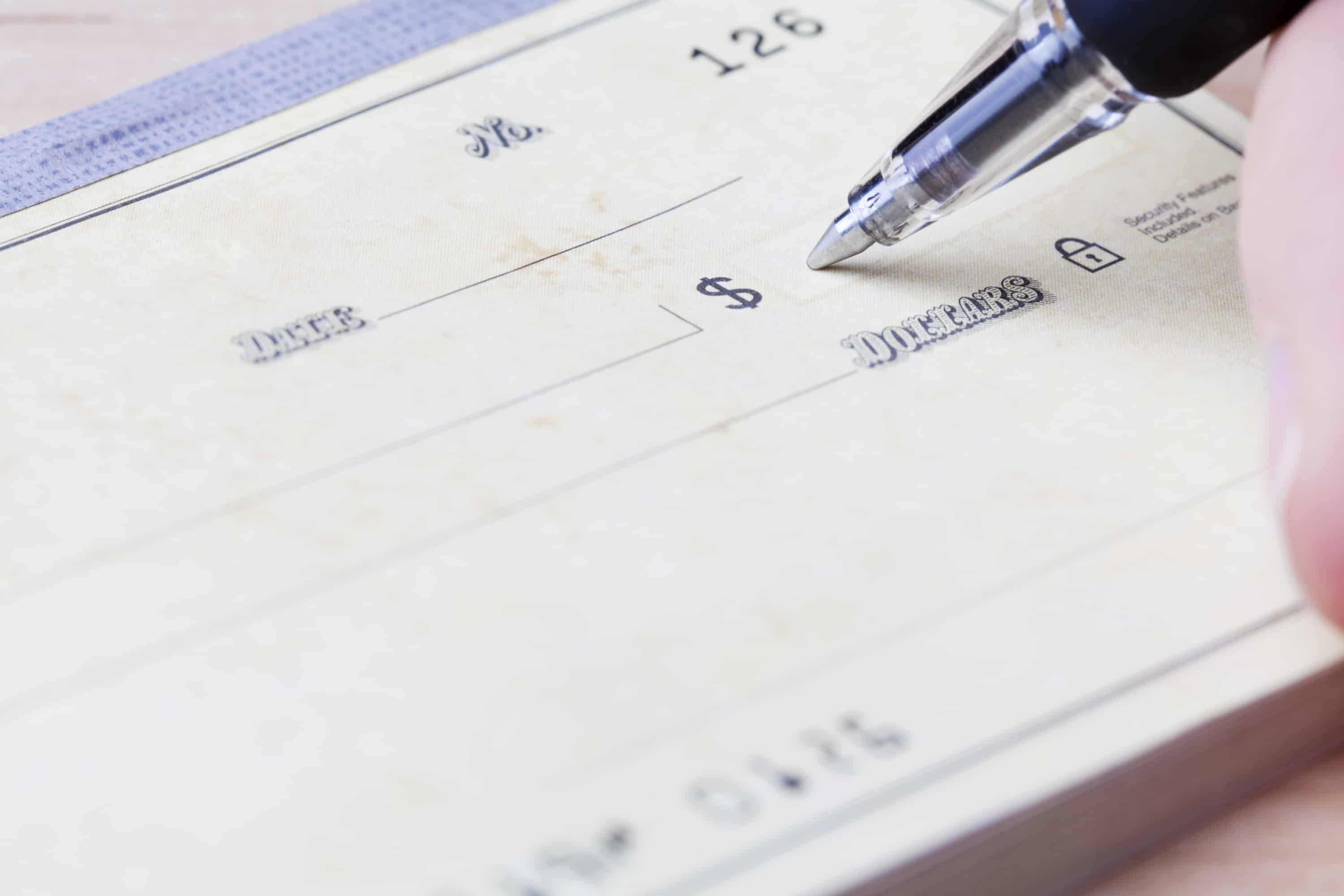 Closeup of a hand filling out a check with a black ballpoint pen