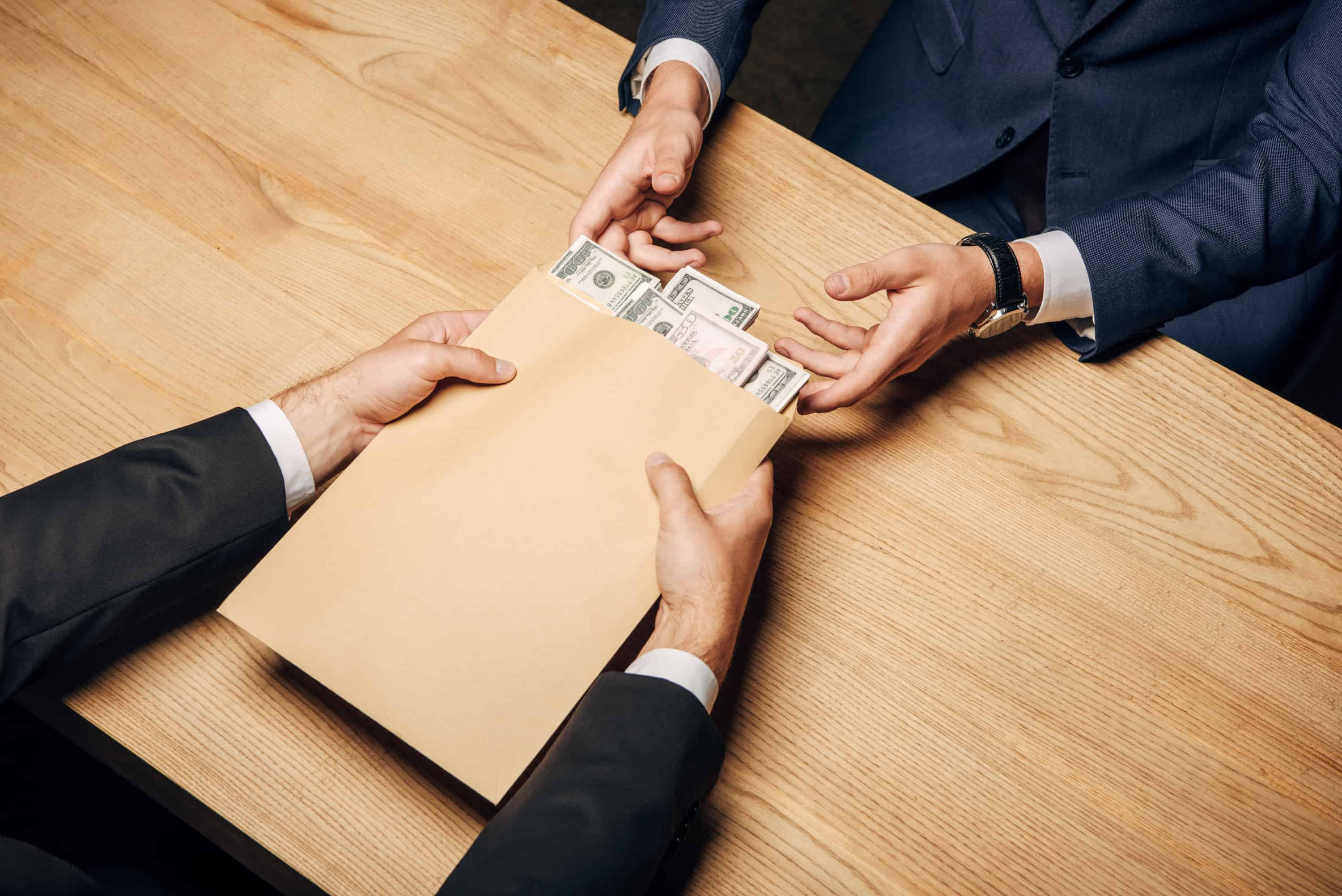 Recovering unclaimed property in a plain brown envelope containing $50 and $100 bills.
