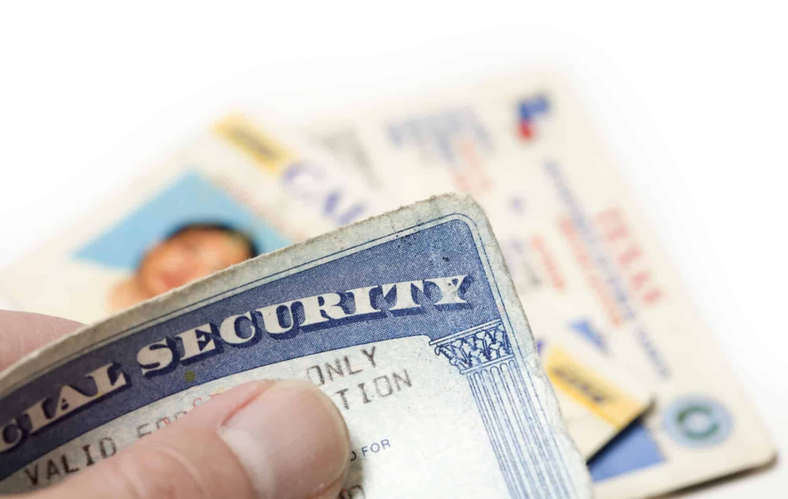Man holding Identity theft documents-social security card, drivers license, voter registration card.