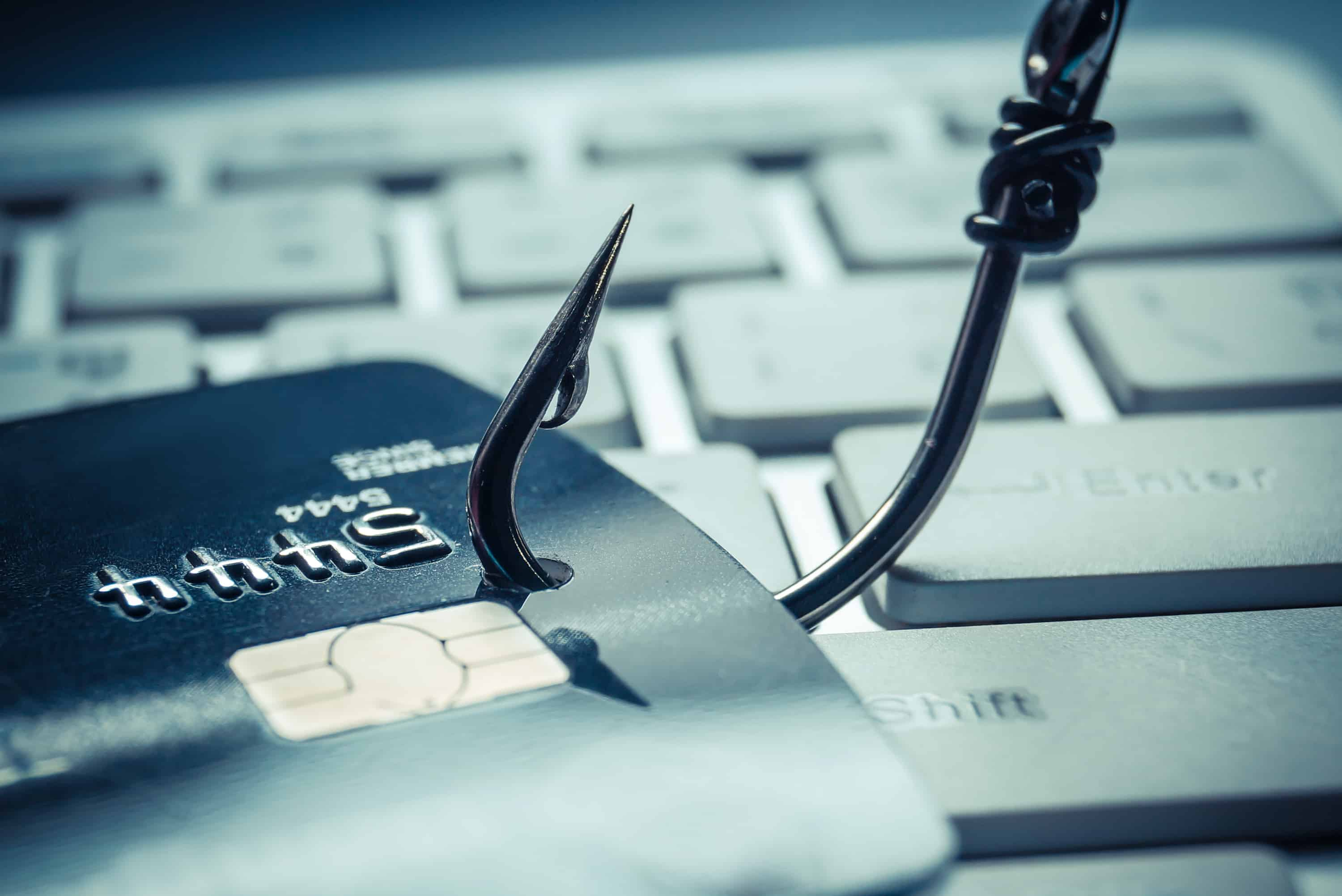 Phishing scam symbolized by a fishing hook put through a credit card sitting on a computer keyboard.