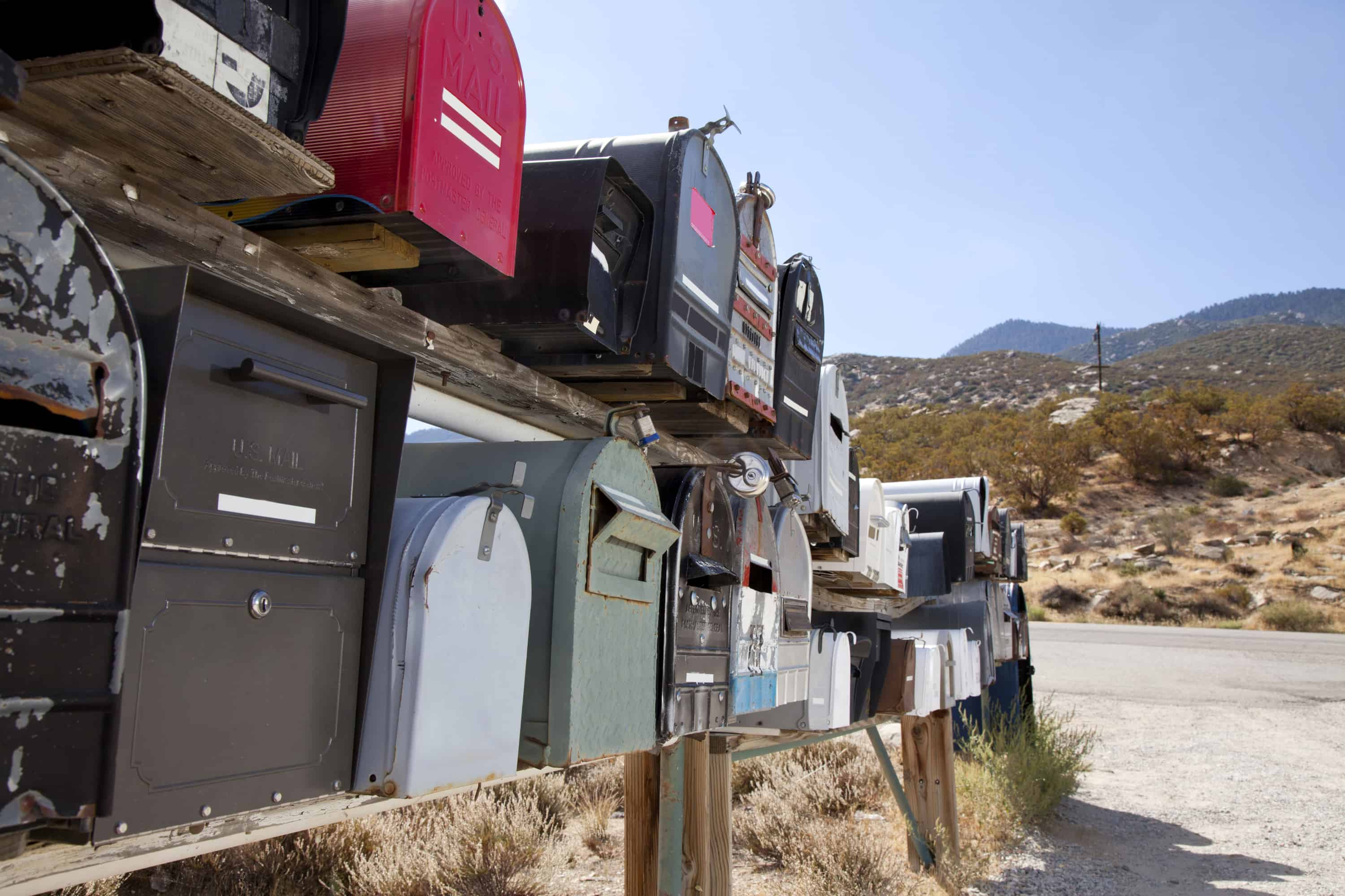 Rows of mailboxes open to identity theft on the side of a rural road.