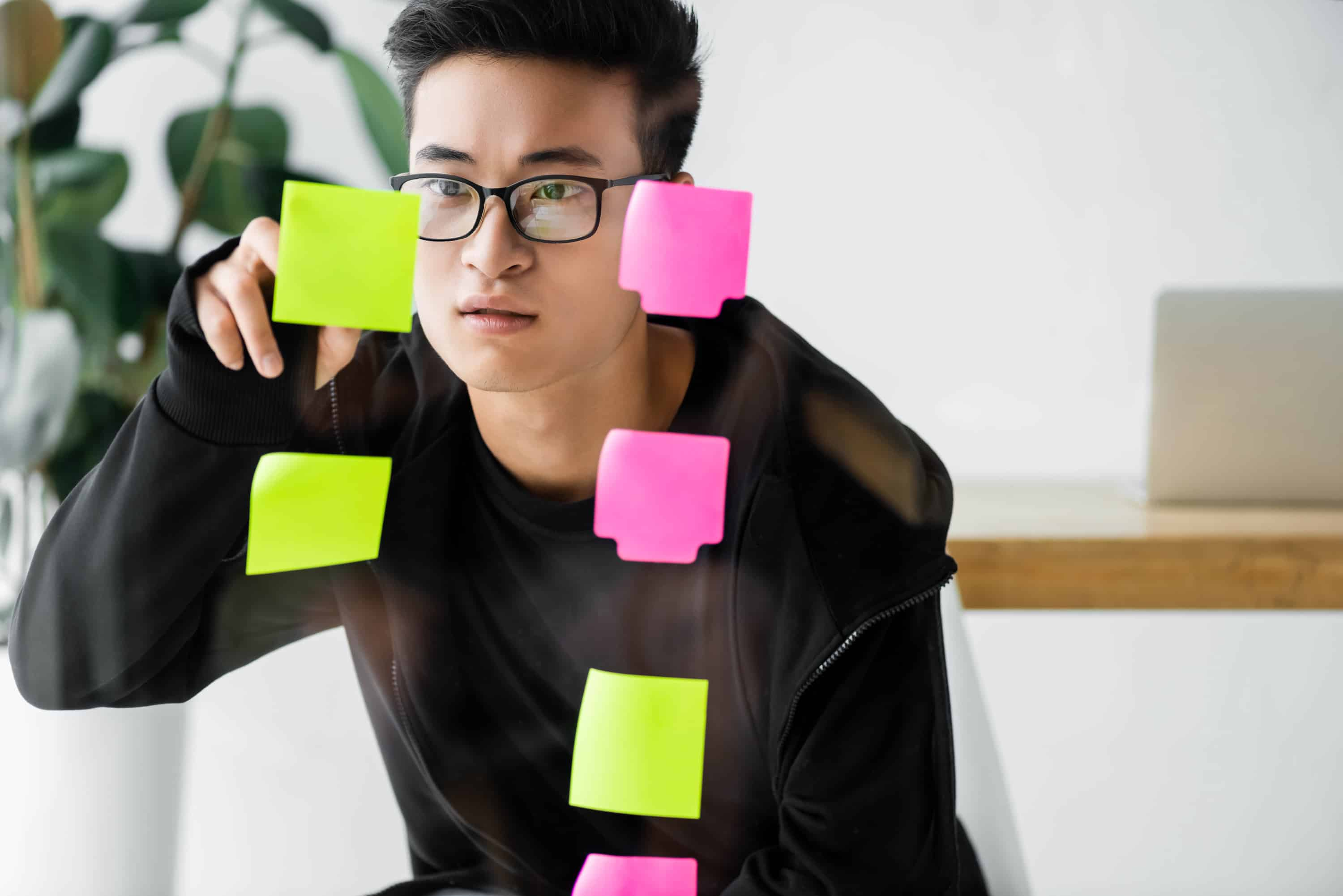 Young Asian man organizing Post-It notes containing a plan to implement financial advice on a glassboard