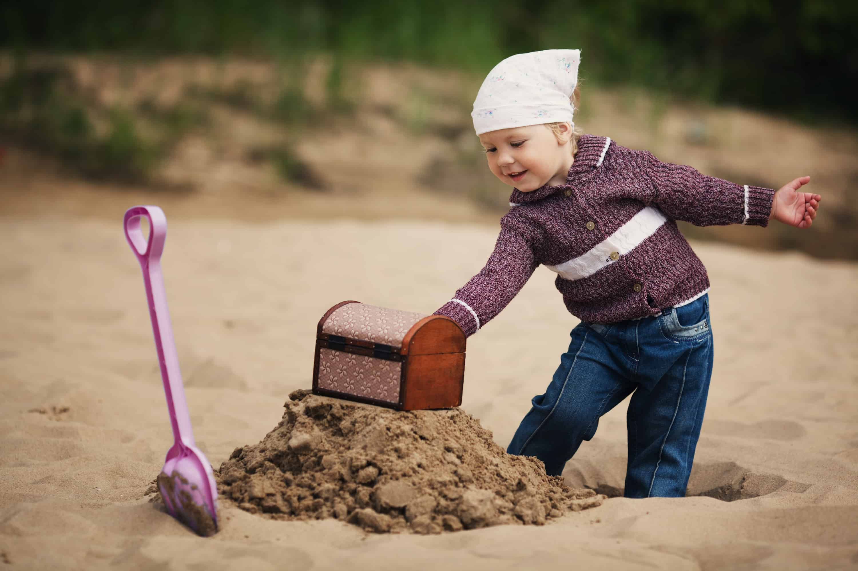 Little girl digging on the beach searching for unclaimed money.