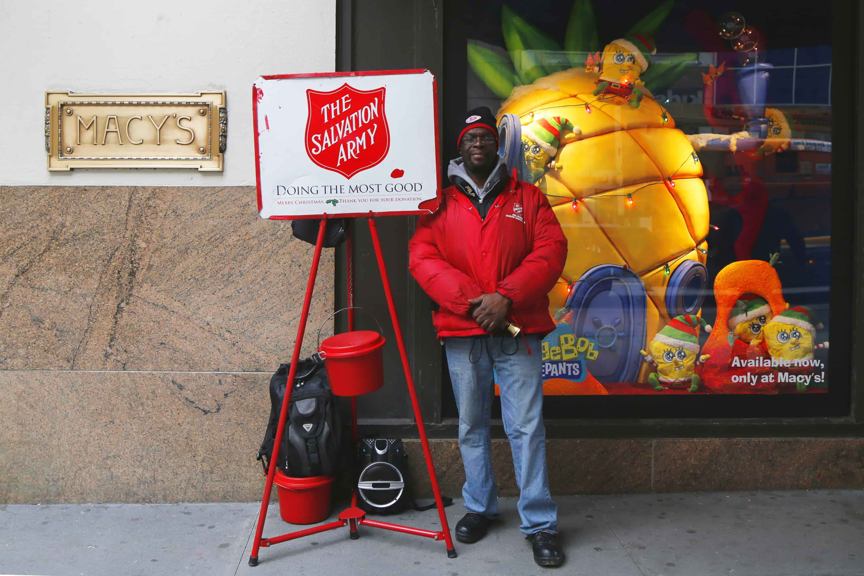 Black male Salvation Army volunteer standing next to the Red Kettle for people to make charitable donations for tax deductions.